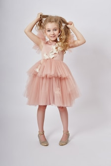 Jong meisje mist schoonheid in een mooie jurk. cosmetica en make-up voor kinderen. meisje die zich voordeed op een licht. grappige emoties en verrassing. ,