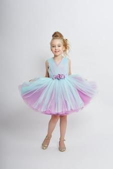 Jong meisje mist schoonheid in een mooie jurk. cosmetica en make-up voor kinderen. meisje poseren op een lichte achtergrond. grappige emoties