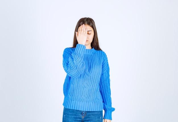 Jong meisje model in blauwe trui coning oog met een hand op wit-grijs.