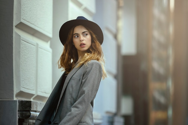 Jong meisje, model, wegkijken, met amerikaans jasje en hoed. op een straatachtergrond.