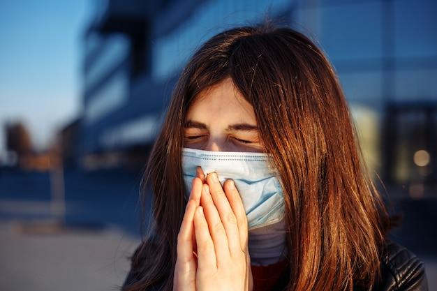 Jong meisje niest en hoest in een medisch masker in de buurt van een gesloten shoppong-winkelcentrum.