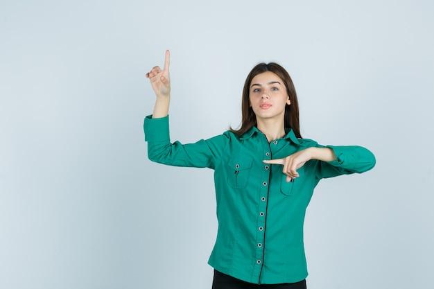 Jong meisje omhoog en links met wijsvinger in groene blouse, zwarte broek en op zoek ernstig. vooraanzicht.