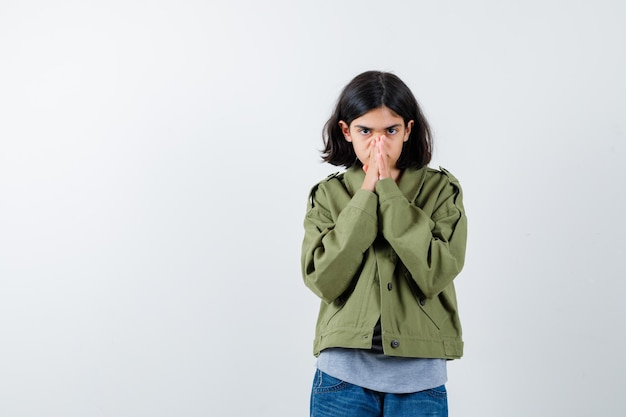 Jong meisje omklemde handen in gebedspositie in grijze trui, kaki jas, jeansbroek en ziet er serieus uit. vooraanzicht.