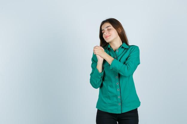 Jong meisje omklemde handen over de borst in groene blouse, zwarte broek en op zoek optimistisch, vooraanzicht.