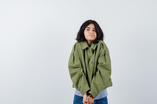 Jong meisje omklemde handen, poserend in grijze trui, kaki jas, jeansbroek en ziet er schattig uit, vooraanzicht.