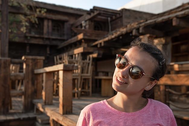 Jong meisje onder de houten details van een groot huis