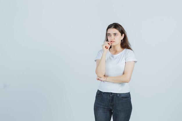 Jong meisje onderlip knijpen in t-shirt, spijkerbroek en op zoek attent. vooraanzicht.