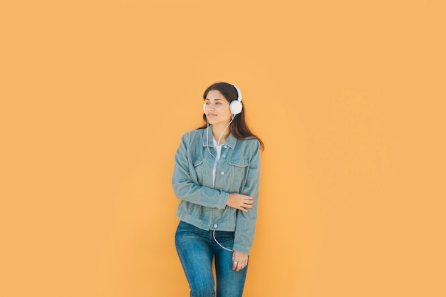 Jong meisje ontspannen luisteren muziek met haar koptelefoon staan voor gele muur