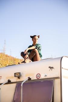 Jong meisje ontspannen op het dak van een retro camper. avontuur in de natuur