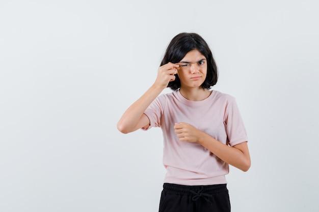 Jong meisje oog met wijsvinger uitrekken in roze t-shirt en zwarte broek en schattig op zoek