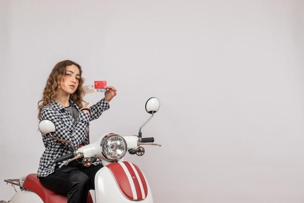 Jong meisje op bromfiets met ticket en kaart op grijs