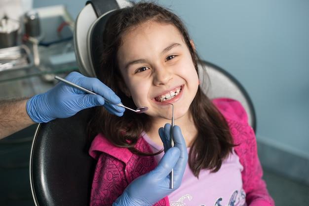 Jong meisje op de eerste tandheelkundige bezoek. hogere mannelijke tandarts die eerste controle voor patiënt doen op het tandkantoor.