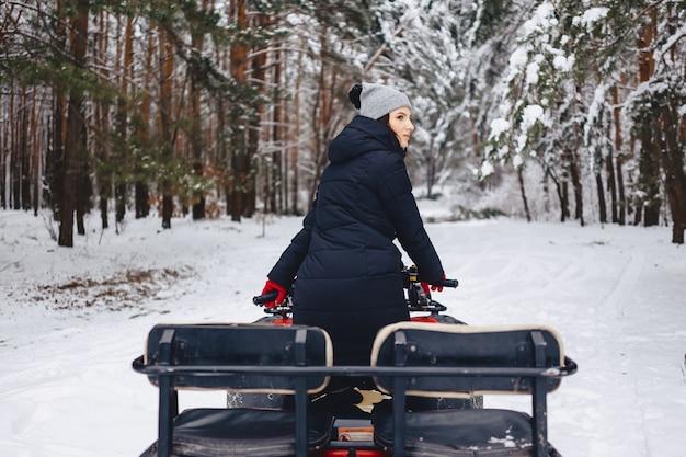 Jong meisje op een motorfietsritten in snow-covered pijnboombos in de winter