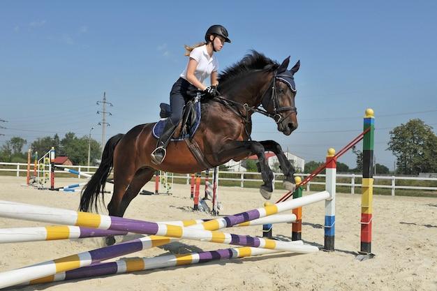 Jong meisje op haar baaipaard springt over een barrière op training.