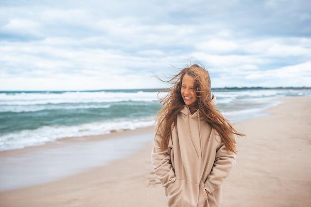 Jong meisje op het strand in bewolkte dag