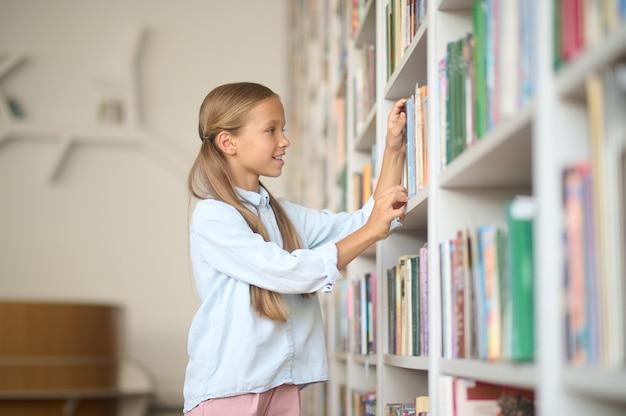 Jong meisje op zoek naar de juiste boeken