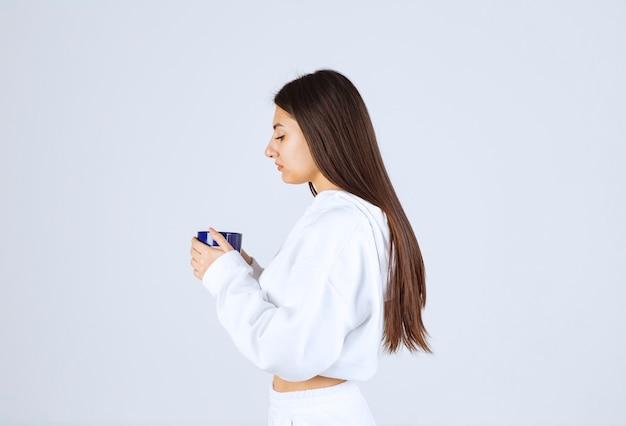 Jong meisje op zoek naar een kopje op wit-grijze achtergrond.