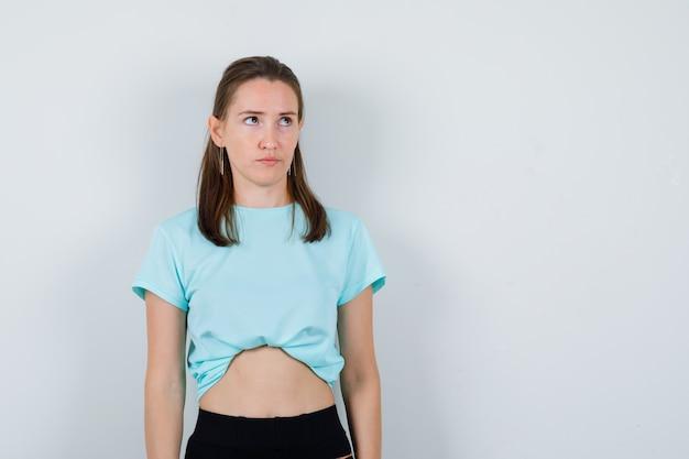 Jong meisje opzoeken in turquoise t-shirt, broek en weemoedig kijken, vooraanzicht.