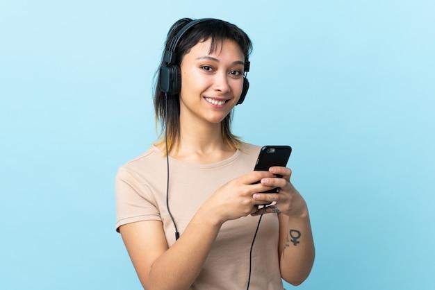 Jong meisje over geïsoleerde blauwe het luisteren muziek met mobiel en kijkend voorzijde