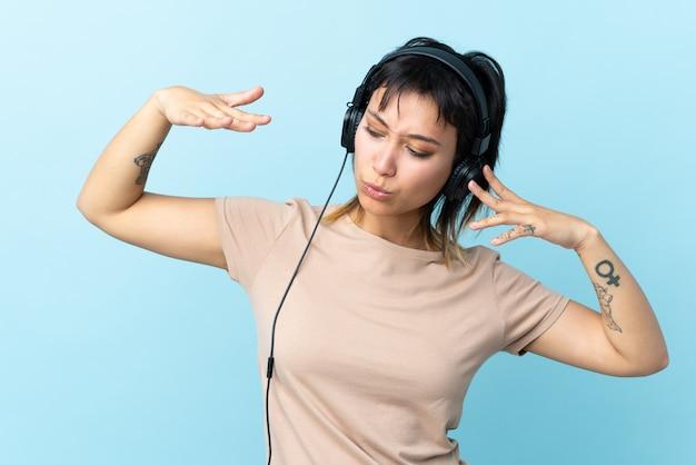Jong meisje over geïsoleerde blauwe muziek luisteren en dansen