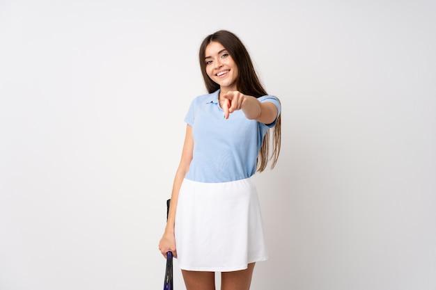 Jong meisje over geïsoleerde witte muur speeltennis en het richten aan de voorzijde