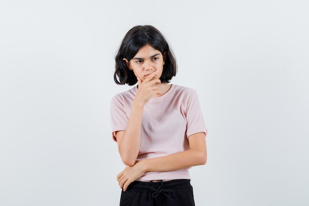 Jong meisje permanent in denken pose, hand op kin zetten in roze t-shirt en zwarte broek en peinzend kijken