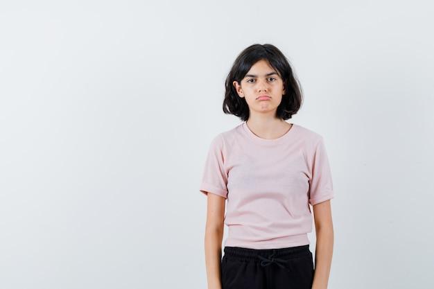 Jong meisje permanent recht en poseren op camera in roze t-shirt en zwarte broek en schattig op zoek