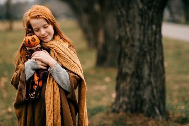 Jong meisje poseren in het park speelgoed knuffelen
