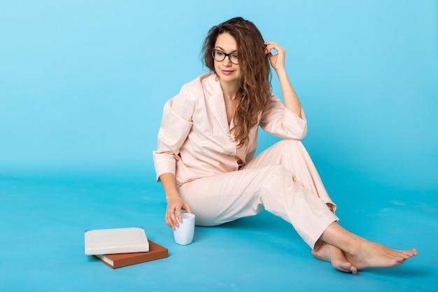 Jong meisje poseren in pyjama's met boeken over blauwe muur. ontspan een goed humeur, levensstijl en nachtkleding