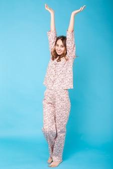 Jong meisje poseren in pyjama's op blauwe muur. ontspan een goed humeur, levensstijl en nachtkledingconcept.