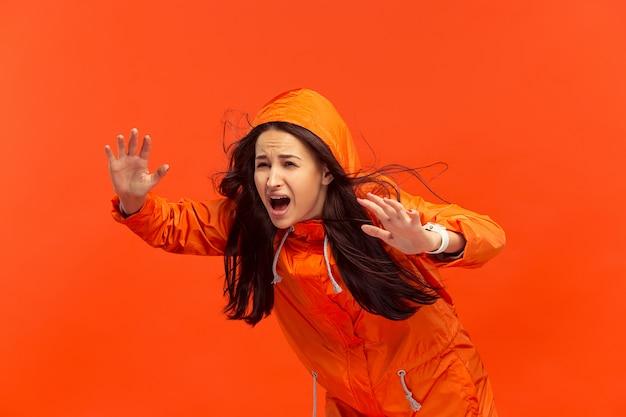 Jong meisje poseren in studio in herfst jas geïsoleerd op rood. menselijke negatieve emoties. concept van het koude weer. vrouwelijke mode-concepten