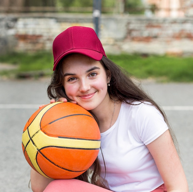Jong meisje poseren met een basketbal