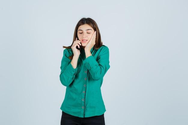 Jong meisje praat met telefoon, houdt hand op wang in groene blouse, zwarte broek en kijkt nieuwsgierig, vooraanzicht.