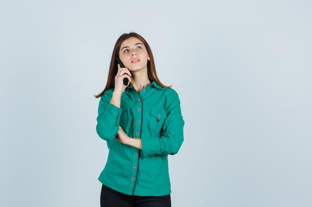 Jong meisje praat met telefoon, kijkend naar boven in groene blouse, zwarte broek en op zoek gericht, vooraanzicht.