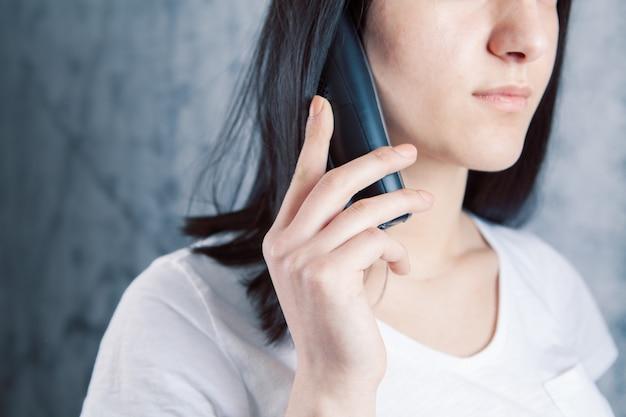 Jong meisje praten aan de telefoon op een grijs