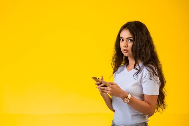 Jong meisje praten en chatten op haar telefoon terwijl ze opzij kijkt.
