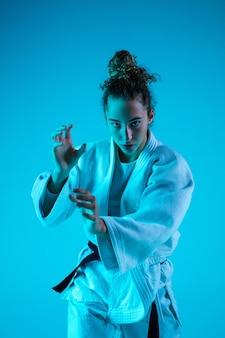 Jong meisje professionele judoïst geïsoleerd op blauw in neon
