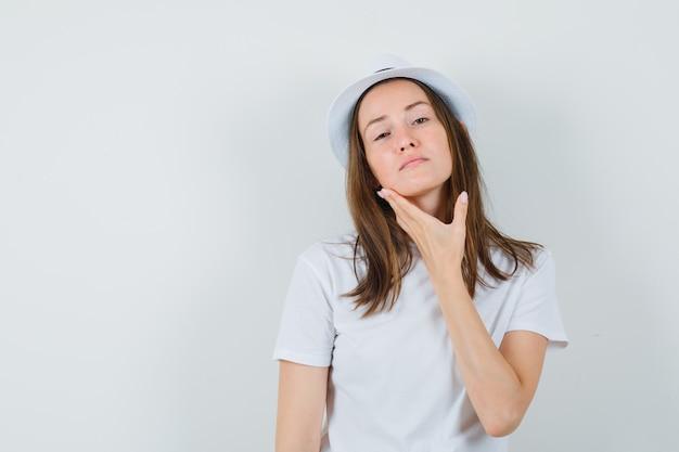 Jong meisje raakt haar kin in een witte t-shirthoed en ziet er elegant uit
