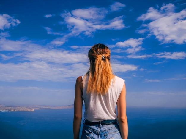Jong meisje reiziger is terug op de zomervakantie tegen de zee en de blauwe lucht