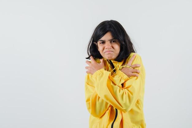 Jong meisje rilt van de kou in een geel bomberjack en ziet er uitgeput uit