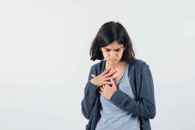 Jong meisje rust handen op de borst in lichtgrijs t-shirt en donkergrijze hoodie met ritssluiting en kijkt gefocust