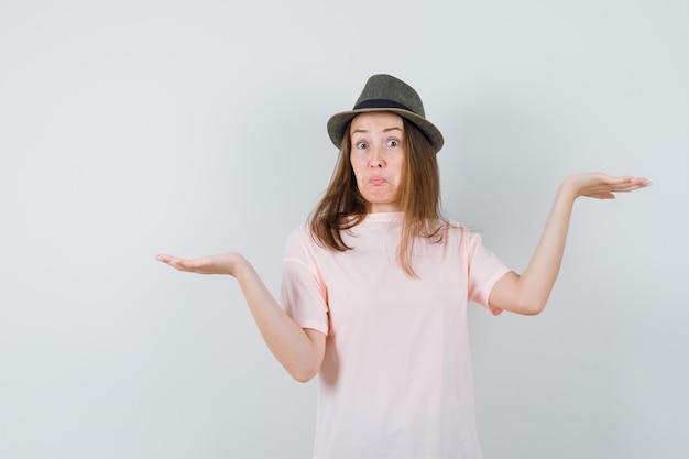 Jong meisje schalen gebaar maken in roze t-shirt, hoed en op zoek verward, vooraanzicht.