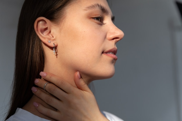 Jong meisje sieraden model in moderne zilveren ronde oorbellen kruisvorm, hand met ring, concept moderne sieraden accessoires winkel, zonlicht