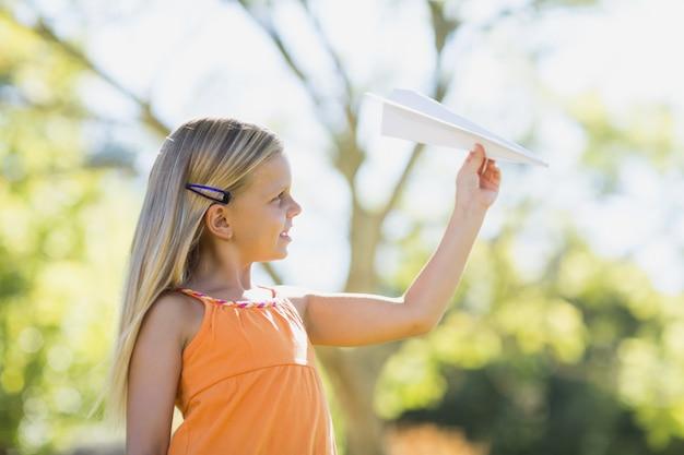 Jong meisje speelt met een papieren vliegtuigje