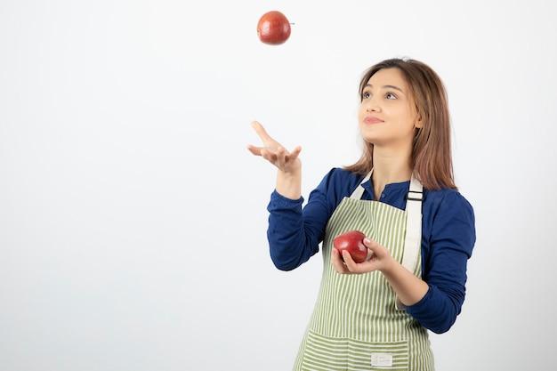 Jong meisje speelt met rode appels op wit.