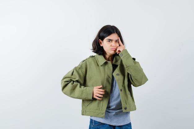 Jong meisje staat in denkende pose in grijze trui, kaki jas, spijkerbroek en kijkt peinzend. vooraanzicht.