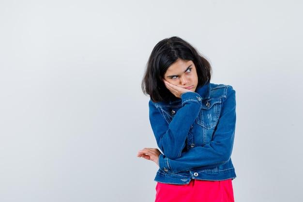 Jong meisje staat in denkende pose in rood t-shirt en spijkerjasje en kijkt peinzend, vooraanzicht.