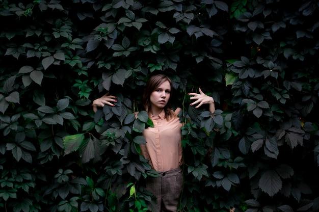 Jong meisje staat in groene bladeren alleen met de natuur, een vrouw raakt planten en dromen aan, een concept van een man in de natuur
