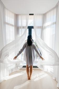 Jong meisje staat met haar rug en opent de gordijnen.