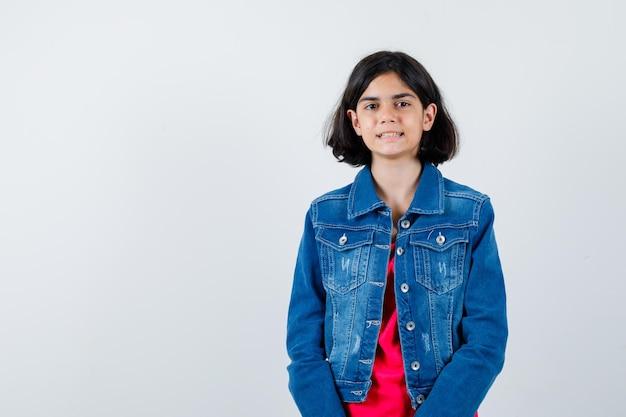 Jong meisje staat rechtop en poseert voor de camera in een rood t-shirt en spijkerjack en ziet er optimistisch uit. vooraanzicht.